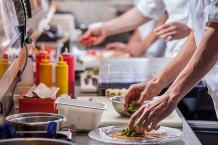 레스토랑 주방에서 식사를 준비하는 남성 요리사 스톡 콘텐츠