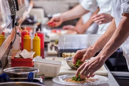 męskie kucharze przygotowują posiłki w kuchni restauracji