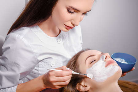 mujer maquillandose: Procedimiento cosmético máscara facial en el salón de belleza Foto de archivo