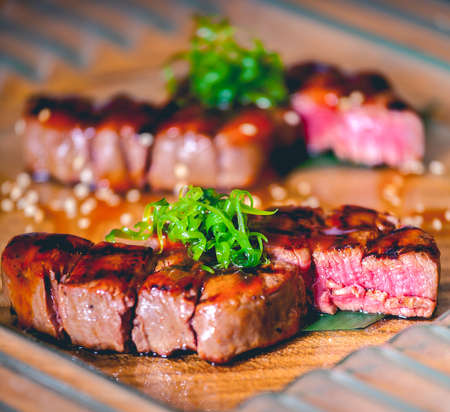 medium close up: Grilled bbq steaks with herbs on wooden table