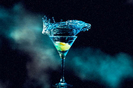 cocktail in glass with splashes and lemon on dark smoky background. Party club entertainment. Standard-Bild
