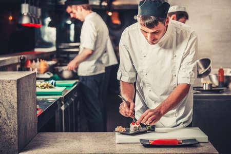 chef cocinando: cocineros de sexo masculino que se preparan sushi en la cocina del restaurante