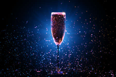 Champagne pouring in glass on black background Stock Photo