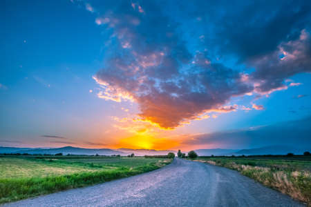 magnificent landscape of road on meadow on background of beautiful sunset sky with clouds Stock Photo