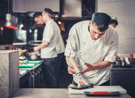male cooks preparing sushi in the restaurant kitchen