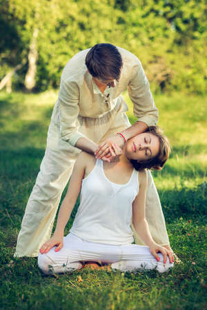 individually: Young man and woman dressed in a white robe doing thai massage with yoga exercises sitting on the grass. Sunny summer park with green lawn in the background Stock Photo