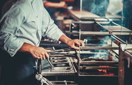 White chef in apron standing near the brazier whith coals, only hands. Man cooking beef steak in the interior of modern professional kitchen Stock Photo