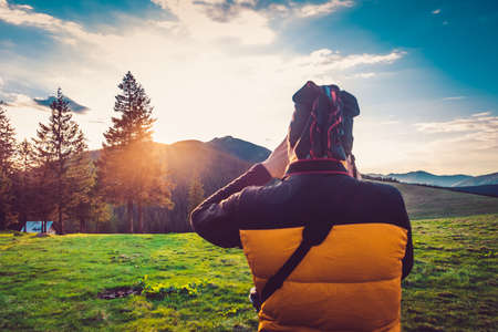 Nature photographer tourist with camera taking a photo in the mountains. Dreamy sunset landscape, spring green meadow and mountain top in the bsckground. Back view. Beautiful nature landscape. Travel background. Stock Photo