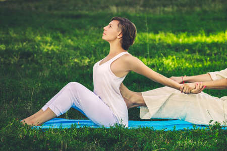 Young man and woman dressed in a white robe doing thai massage with yoga exercises sitting on the mat. Sunny summer park with green lawn in the background Stockfoto