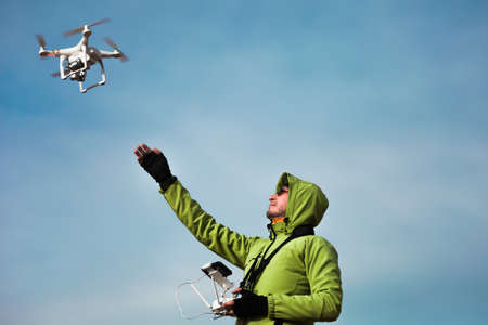 Young man in green jacket operating a drone using a remote controller. Stock Photo