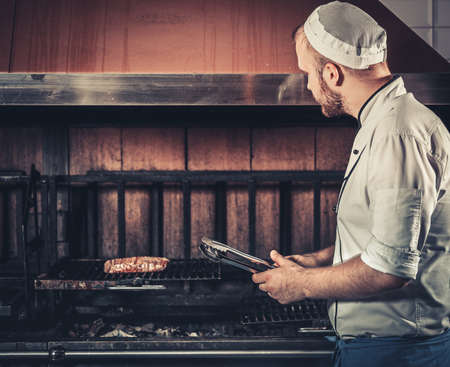 brazier: Young white chef in blue apron and hat standing near the brazier whith coals. Man cooking beef steak in the interior of modern professional kitchen Stock Photo