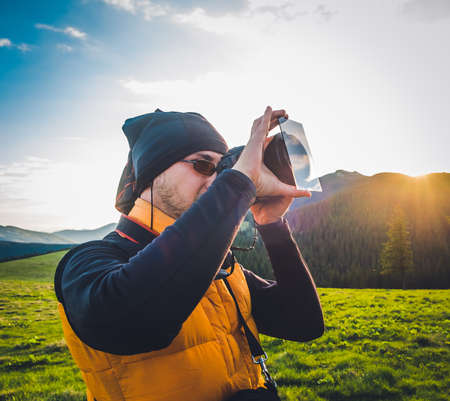 Nature photographer tourist with camera taking a photo in the mountains. Dreamy sunset landscape, spring green meadow and mountain top in the background photo