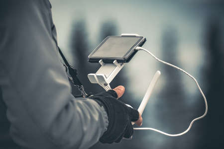 Man operating a drone using a remote controller. Winter holidays in mountains. Close up picture. Bukovel, Carpathians, Ukraine, Europe. Exploring beauty world photo