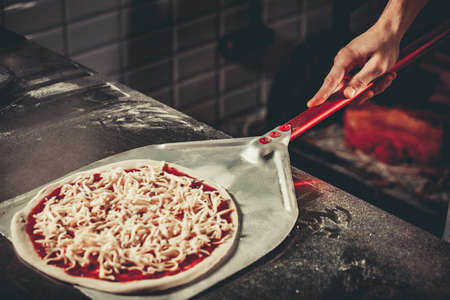 woodfired: Food concept. Preparing traditional italian pizza. Chef holds long irob shovel for pizza, baking dough with pasta and cheese in a professional oven. Only hands close up Stock Photo