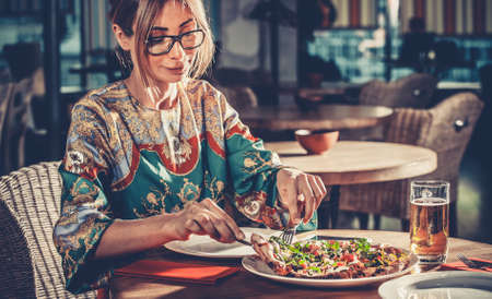 Food concept: Young blonde beautiful woman in colorful dress have a lunch in interior of modern restaurant. She sits at the table with white plate, beer glass and delicious italian pizza with herbs Imagens