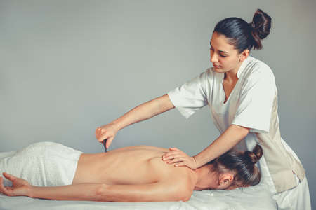 Massage gua, sha therapy. A young professional female masseur makes Thai massage. Patient is lying down on a bed and is covered with white towel. Treatment, rest, relaxation, health care, medicine