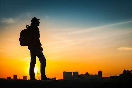 Traveler silhouette watching amazing sunset. Young casual man with backpack and cowboy hat standing alone on hill above evening cityscape. Lifestyle Travel Concept Outdoor Background. Kiev, Ukraine photo