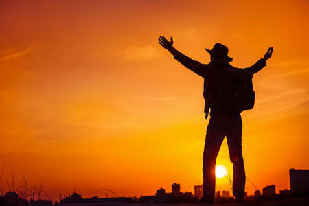 Traveler silhouette of man looking on sunset sky celebrating enjoying freedom, victory, success. Business concept and hands up. Orange toning filter. Lifestyle Travel Outdoor Background. Kiev, Ukraine photo