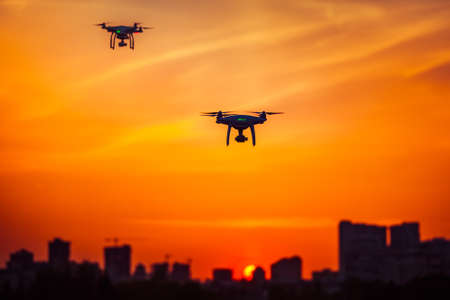 Two modern Remote Control Air Drones Fly with action cameras in dramatic orange sunset sky. Cityscape silhouette in the background. Modern technologies. Kiev, Ukraine. Travel, hobby, inspiration Stock Photo