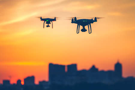 Two modern Remote Control Air Drones Fly with action cameras in dramatic sunset sky. Cityscape silhouette in the background. Modern technologies. Close up. Kiev, Ukraine. Travel, hobby, inspiration