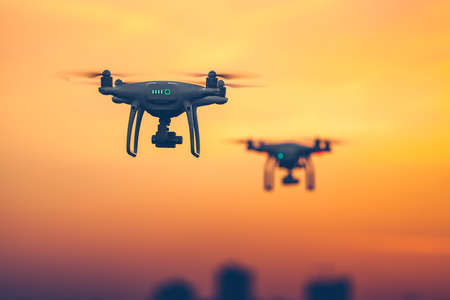 Close up photo of two Professional Remote Control Air Drones with action cameras flying in dramatic sunset sky. Modern technologies. Travel, hobby, inspiration. Pastel orange toning. Kiev, Ukraine 版權商用圖片