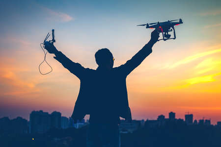 Silhouette of man holding switched on Drone quad copter and Remote control enjoying freedom, victory, success. Cityscape with dramatic colorful sunset sky in the background. Business concept, hands up