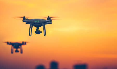 Two Professional Remote Control Air Drones with action camera flying in dramatic sunset sky. Modern technologies. Travel, hobby, inspiration. Pastel orange toning. Horizontal copy space. Kiev, Ukraine 版權商用圖片 - 78565200