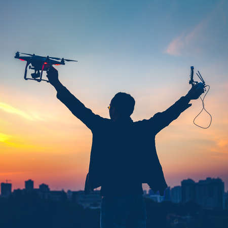 Silhouette of man holding switched on Drone quad copter and Remote control enjoying freedom, victory, success. Cityscape with dramatic sunset sky in the background. Business concept, raised hands photo