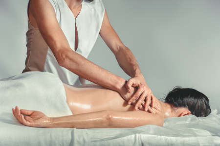 lymphatic drainage therapy: Massage oil therapy. A young professional male masseur makes Thai massage. Patient woman is lying down on a bed and is covered with white towel. Treatment, rest, relaxation, spa, health care, medicine