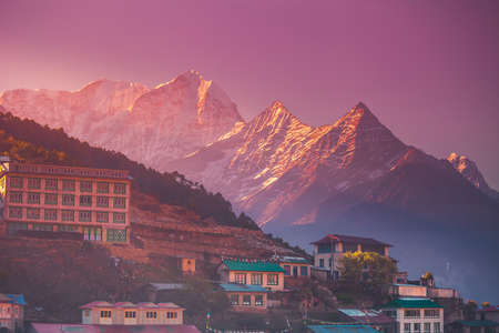 Amazing sunrise view of Namche Bazaar village hotels against mountain peak, Khumbu valley, Nepal. Trekking route to Everest Base Camp, Himalayas. Holidays, sport, recreation. Pink retro vintage toning