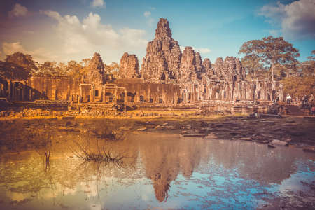 Angkor Wat Temple in Cambodia reflected in lake. Largest religious monument complex in the world. Ancient Khmer architecture. Orange ancient ruins against blue sky. Retro vintage toning
