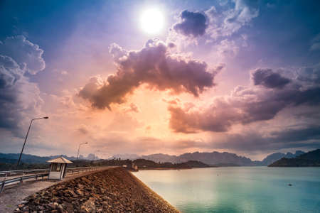 Ratchaprapa Dam or Chiao Lan reservoir , Suratthani Thailand. Colorful sunset cloudy sky in the background. Nature landscape Stock Photo