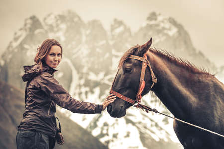 Portrait of young pretty cheerful woman with horse in mountain valley. Horse and girl outdoors, womans hand makes a friendly gesture to a horse by stoking its head. Vintage Color filter toning