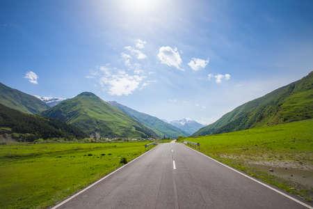 Berg lege weg met groene heuvels en blauwe zonnige hemel. Bergen van de Kaukasus, kloven, wolken, een smalle weg, hoge bergen - dit alles is de militaire Georgische weg.