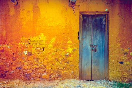 Stijlvolle gekraakt vintage kleurrijke muur in geeloranje tinten met koninklijk blauwe houten deur. Ideale achtergrond voor retro-stijlillustraties en collages. Grunge-stijl. Artistieke retouchering. Stockfoto