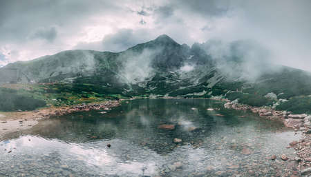 The fairy tale misty landscape the mountain Kalnate pleso lake surrounded by the mighty Tatras. Tatranska Lomnica, Slovakia. Ideal background in grey shades for the collages and illustrations. Фото со стока