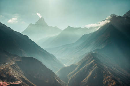 The breathtaking panoramic view the mighty misty snow-capped Himalayas and the canyons with the coniferous forests. Nepal. Ideal background for the various kinds of collages and illustrations. Stock Photo