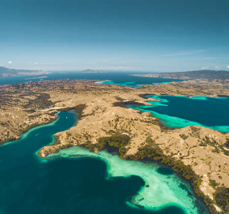 Bays, savanna lands, ocean. Komodo Aerial shot. Spectacular panoramic view from above the stunning bays and savanna territory of Komodo National Park. Indonesia. Heritage Site. Overview drone shot.