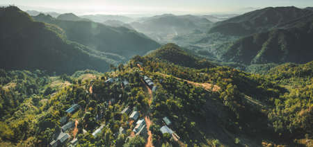 Settlement among Thailand wild nature. Aerial drone shot of green covered valley. Sunlit North Thai hills. Overwhelming Asian landscape. Buildings among the wild environment. Standard-Bild