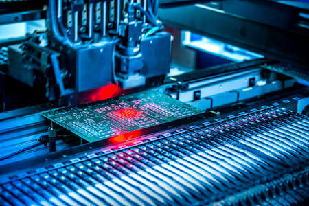 Circuito electrónico debajo de la máquina de montaje en superficie. Filmada en tintes rojos y azules. Tecnología de montaje en superficie como producción de circuitos electrónicos. Componentes colocados sobre la superficie de elementos impresos. Foto de archivo