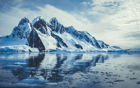 Ice covered mountains in polar ocean. Winter Antarctic landscape in blue and white tints. The mounts reflection in the crystal clear water. The cloudy sky over the massive glacier. Travel wild nature