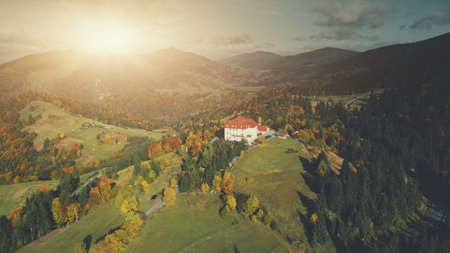 Colorful Sunset Mountain Peak Aerial View. Majestic Highland Landscape, Wild Forest Scenery, Natural Environment. Hill Countryside Village Hotel. Tourism Travel Concept. Drone Flight