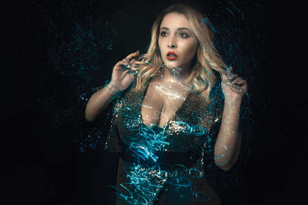 Fashion portrait of young woman in shiny decollete evening dress. Mixed blue lights effects. Close-up blonde in sequins wear. Stylish glamour look. Expression of surprise on face. Black background. Stok Fotoğraf