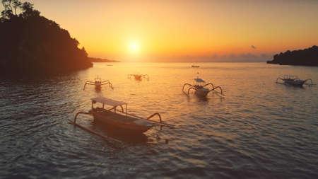 Drone Flight over Sunset Ocean. Boats sailing in soft orange light. Travel Vacation Recreation Paradise Tourism. Beautiful nature landscape in Tropical Nusa Penida Bali Island, Indonesia