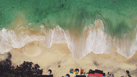 Aerial Drone View: Ocean Beach Waves in Sunny Day. White sand and crystal water landscape in Tropical Bali Island, Indonesia. Travel Vacation Recreation Paradise Tourism Concept. Top down
