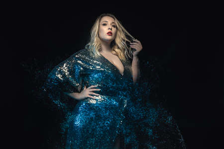 Half length plus size model shot with mixed lights effect. Black background. Young blonde woman in shiny evening dress posing towards the camera. Fashion glamour shooting. Stock fotó