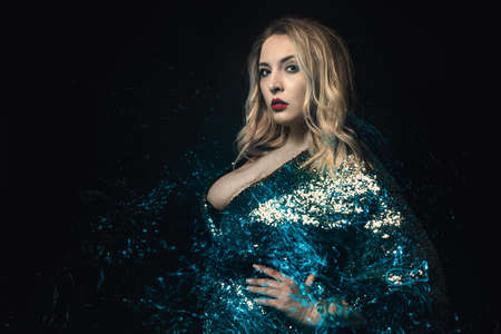Blond Woman with Blue Bright Sparkles Element Copy Space. Standing Fashionable Girl Plus Size Model Studio Photo Black Background. Glamor Positive Caucasian Female Looking Away Front View