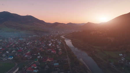 picturesque mountain town on wide river bank among hill silhouettes and bright sunset behind hilltop aerial view. Carpathian mountains, Ukraine beauty nature. Travel, summer holidays.