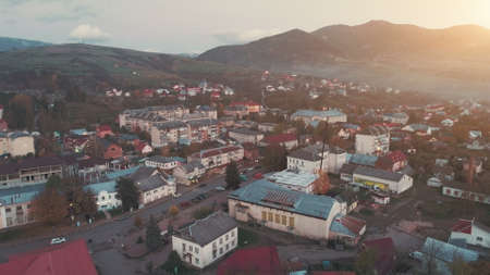 town neat streets with cars driving along grey road surrounded by buildings among hill silhouettes in evening upper view. Carpathian mountains, Ukraine beauty nature. Travel, summer holidays.