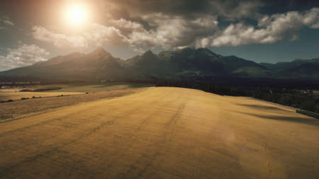 Aerial View Drone Flight above dramatic mountain range and yellow ripe wheat field in golden light sunset. Dramatic picturesque landscape. Tatras Mountains, Slovakia. Vintage retro toning filter.